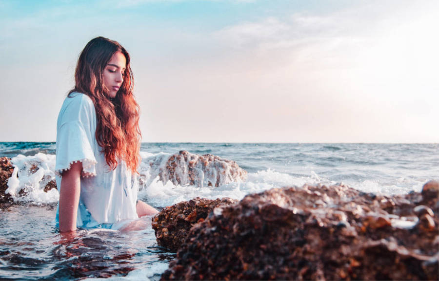 girl sitting in the water asking herself how to become a mermaid