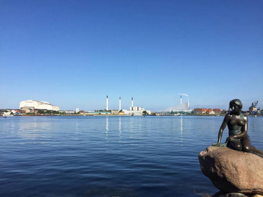 Statue der kleinen Meerjungfrau mit Gebäuden im Hintergrund