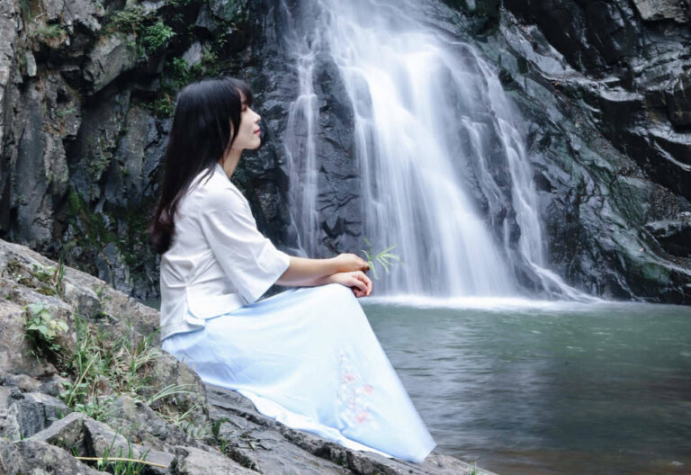 A water spirit sitting in front of a waterfall