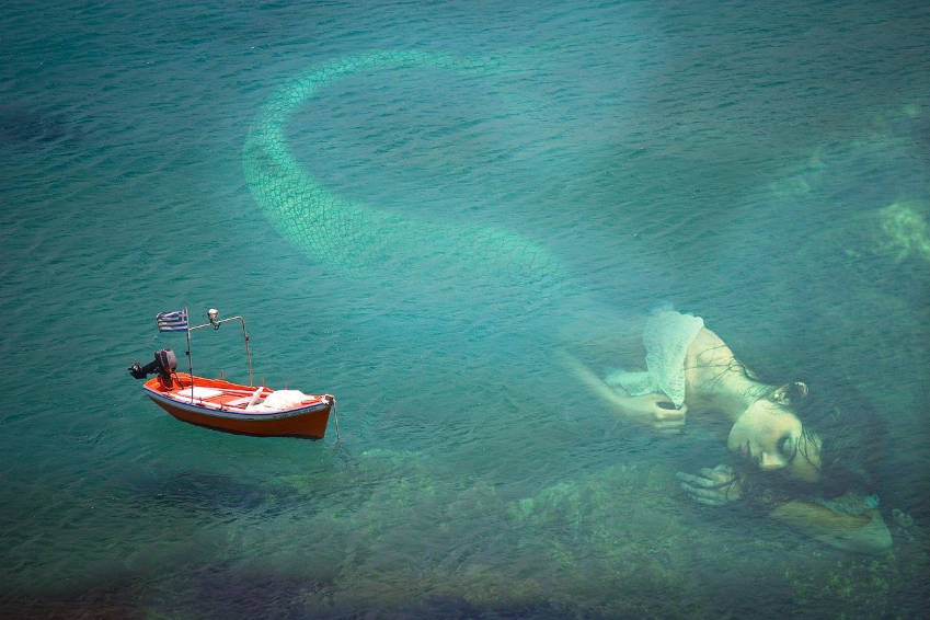 a giant mermaid under the surface of the ocean next to a boat