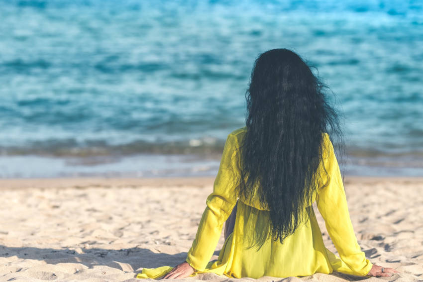 woman with long hair sitting on beach, what is the mermaid hair challenge